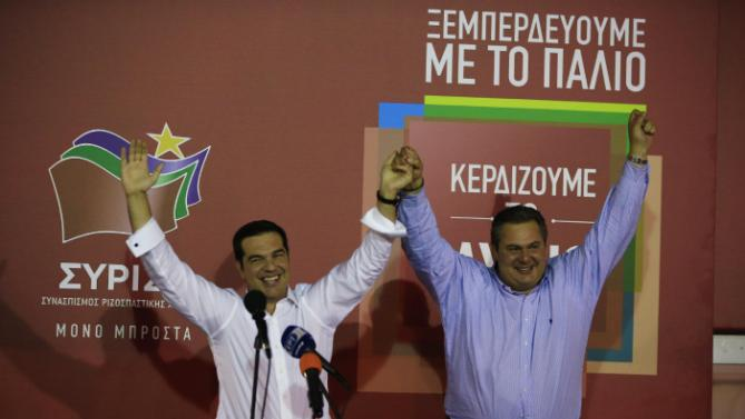 Left-wing Syriza party leader Alexis Tsipras, left, and leader of the right-wing Independent Greeks party Panos Kammenos raise their hands as they greet from supporters at Syriza's party's main electoral center in Athens, Sunday, Sept. 20, 2015. Tsipras who won Greece's parliamentary election for the second time this year on Sunday, says he will form a coalition government with the small right-wing Independent Greeks. (AP Photo/Lefteris Pitarakis)